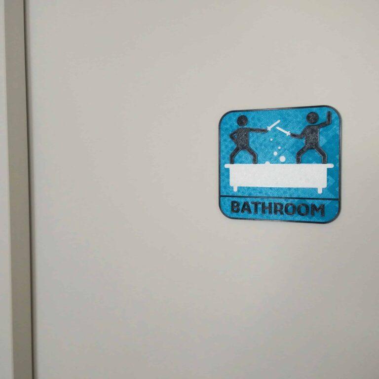 blue black and white bathroom door sign